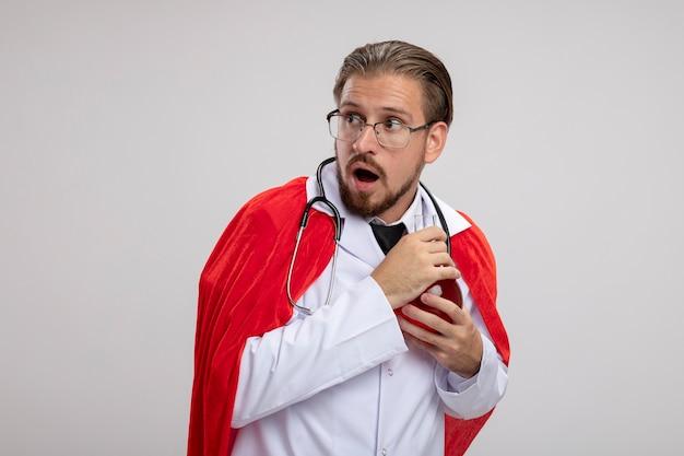 Gars jeune super-héros gourmand portant une robe médicale avec stéthoscope et lunettes tenant une bouteille en verre de chimie remplie de liquide rouge isolé sur fond blanc