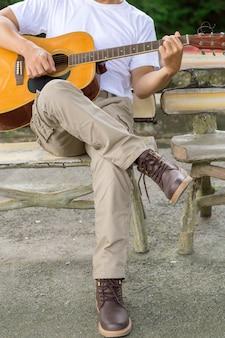 Le gars joue de la guitare, en plein air, pantalon cargo