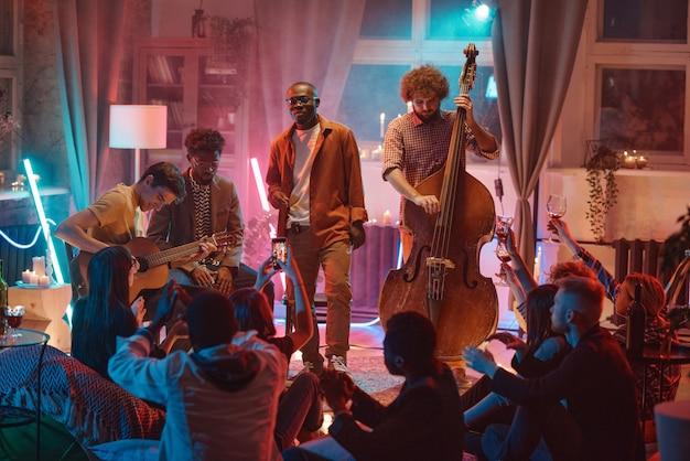 Les gars jouent sur différents instruments de musique pour les gens pendant leur performance dans la boîte de nuit