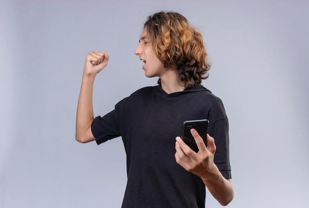 Gars joyeux aux cheveux longs en t-shirt noir tenant un téléphone et lever son poing sur un mur blanc