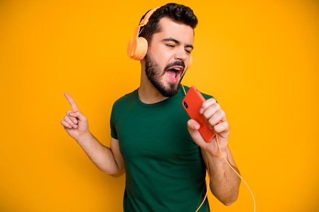 Un gars joyeux positif écouter de la musique stéréo à partir d'un casque orange utilise un téléphone portable comme micro