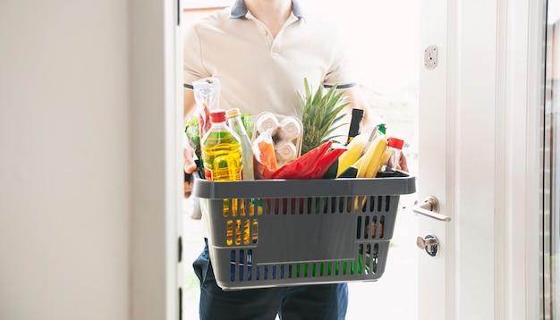Le gars livre le panier plein de courses à la porte de la maison. shopping en ligne.
