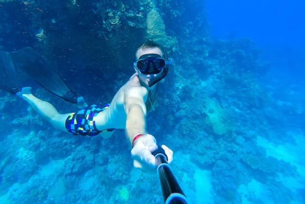 Un gars avec un masque et un tuba plonge dans les eaux bleues de la mer rouge et se photographie