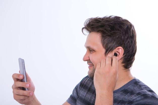 Le gars met un casque sans fil dans son oreille et commence à parler au téléphone en utilisant une liaison vidéo. écouter de la musique