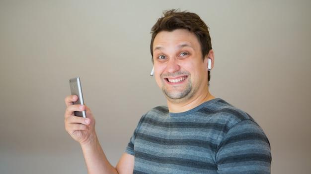 Le gars met un casque sans fil dans son oreille et commence à parler au téléphone en utilisant un lien vidéo