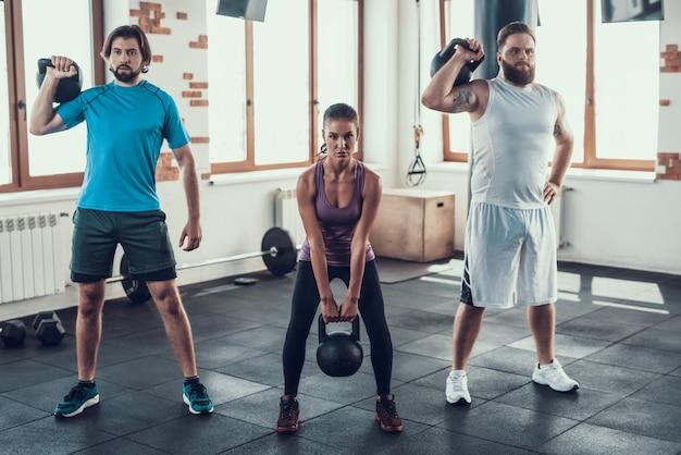 Les gars mettent des poids sur leurs épaules et une fille fait un squat.