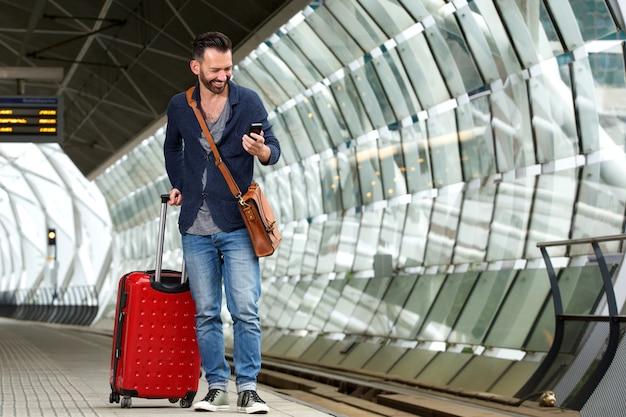 Gars mûr sur la plate-forme ferroviaire avec sac et téléphone mobile