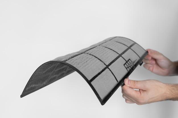 Le gars nettoie le filtre du climatiseur domestique de la poussière. filtre de climatiseur très sale. entretien des équipements climatiques.