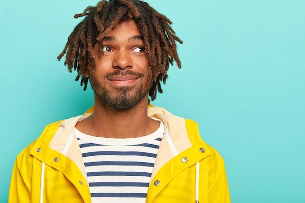 Un gars pensive attrayant avec un regard heureux, concentré sur le côté, a une moustache, une barbe et des redoutes, porte un pull et un imperméable de marin décontracté, pense à ses projets le week-end, se tient contre le mur bleu