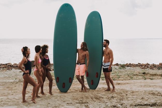 Les gars à la plage détient surfs. filles en maillot de bain.
