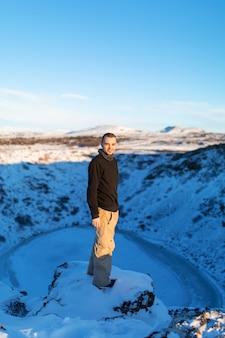 Le gars près du lac gelé kerid dans le cratère du volcan.