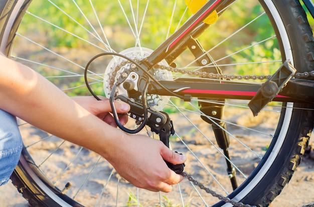 Le gars répare le vélo. réparation de la chaîne. cycliste. unratitude sur la route, voyage, gros plan.