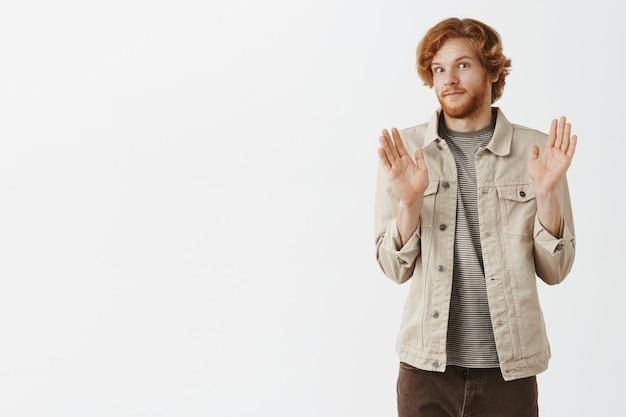 Gars rousse barbu maladroit posant contre le mur blanc