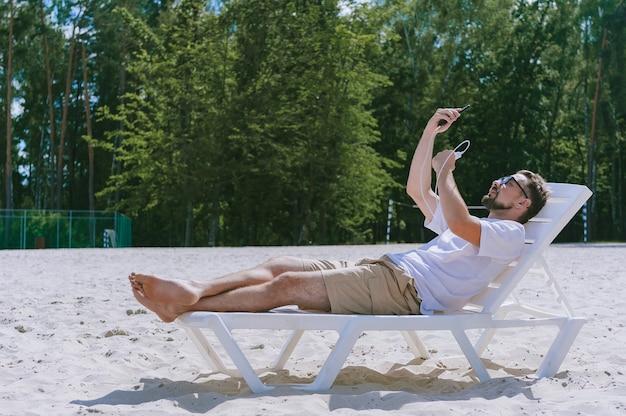 Le gars s'allonge sur une chaise longue, prend un selfie sur son smartphone et charge depuis le power bank. sur fond de plage et de forêt.