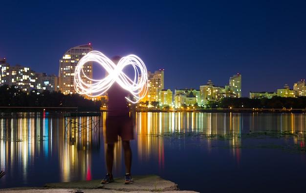 Un gars se tient sur les rives du dniepr dans le contexte d'un remblai de nuit lumineuse