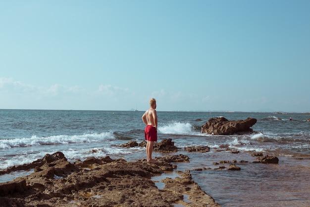 Le gars se tient sur les rochers au bord de la mer