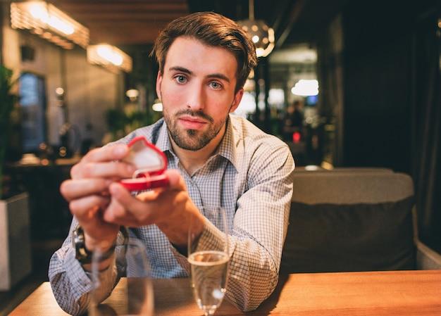 Un gars sérieux et barbu est assis à la table et montre une boîte avec une bague. il attend une réponse de sa copine