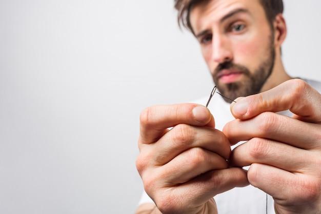 Un gars sérieux et concentré essaie de faire passer un fil dans le chas d'une aiguille. il le fait très précisément. fermer. vue en coupe. isolé sur mur blanc.