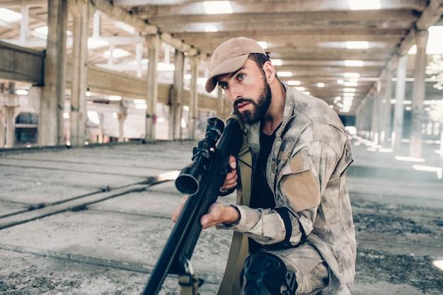 Un gars sérieux fait attention aux sons dans un grand bâtiment vide. il est dans le hangar. le soldat tient un gros fusil et regarde droit devant. l'homme est prêt à tirer.