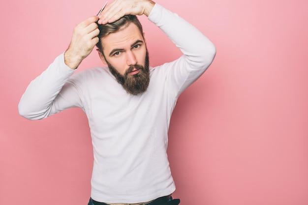 Un gars sérieux se brosse les cheveux. il fait cela très tendre et précis. l'homme regarde aussi vers le bas. isolé sur fond rose.