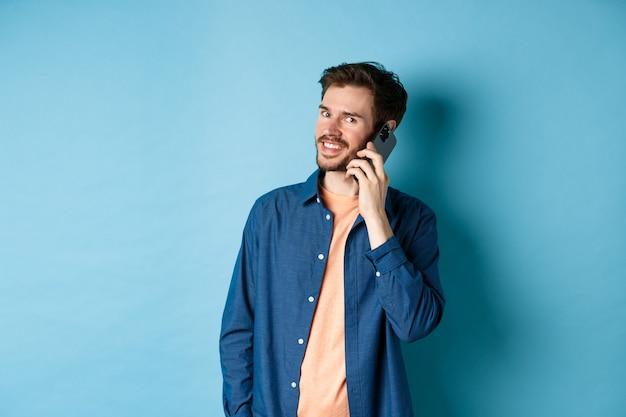 Gars souriant moderne parlant au téléphone mobile, regardant heureux à la caméra, debout sur fond bleu.