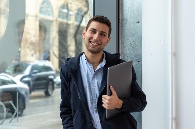 Un gars sourit et détient un ordinateur portable