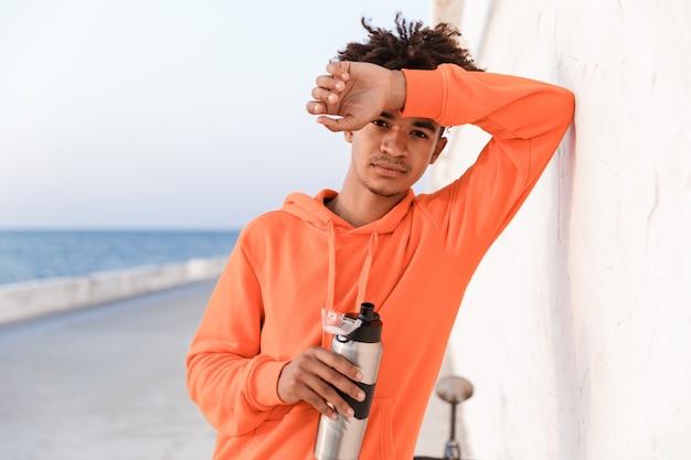 Gars de sport à l'extérieur sur la plage d'eau potable tenant une bouteille