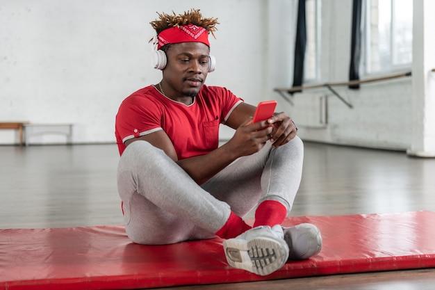 Un gars sportif attentif se reposant après un entraînement intense tout en regardant sur son smartphone et en choisissant la chanson appropriée