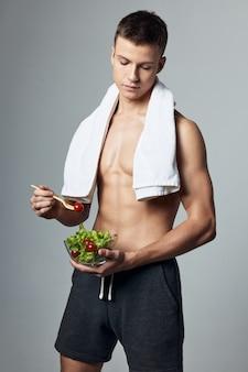 Gars sportif mangeant des salades, mangeant sainement, repas post-entraînement