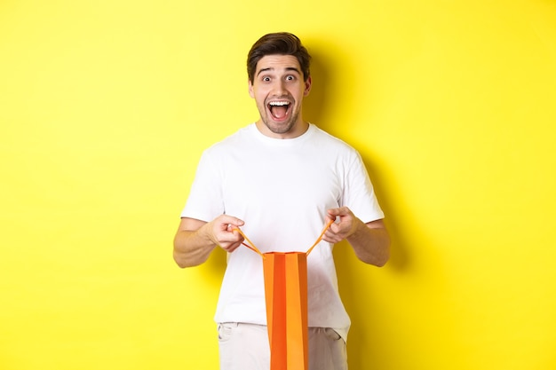 Un gars surpris ouvre le sac à provisions avec le poing, l'air excité et heureux devant la caméra, debout sur fond jaune