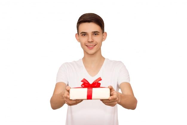 Le gars en t-shirt blanc fait un cadeau, isoler, un gars attentionné prépare un cadeau à sa petite amie