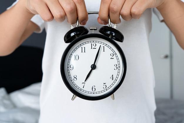 Un gars en t-shirt blanc tient un réveil noir élégant avec une cloche. au réveil, début du huitième. c'est l'heure de se lever.
