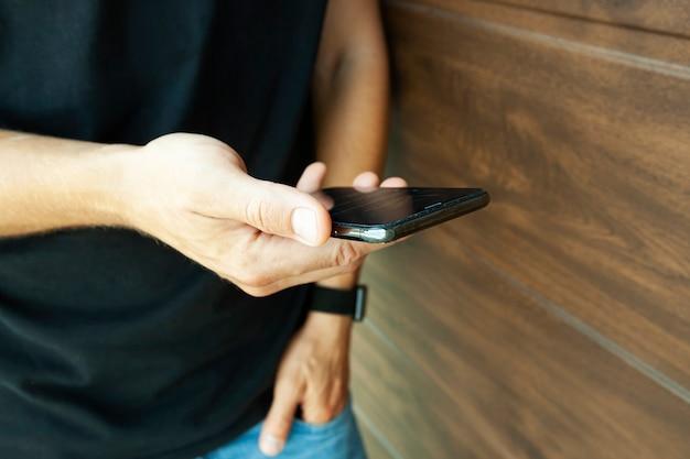 Le gars en t-shirt noir vérifiant ses réseaux sociaux dans son téléphone près du mur en bois