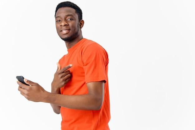 Gars avec téléphone portable apparence africaine tshirt orange fond clair