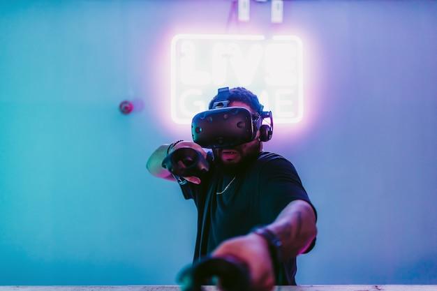 Le gars en tenue de jeu dans la salle néon