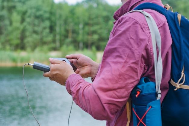 Le gars tient un chargeur portable avec un smartphone à la main. homme sur fond de nature avec verdure et lac.