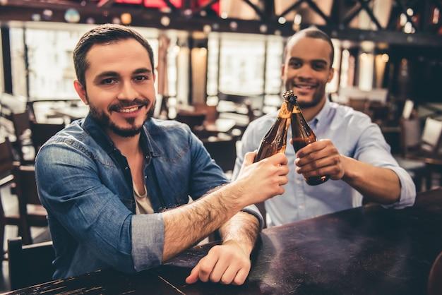 Les gars trinquent des bouteilles de bière tout en se reposant dans un pub.