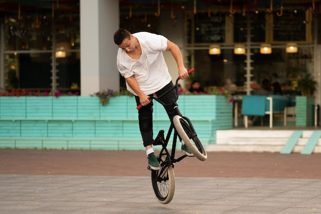 Le gars sur le vélo acrobatique fait la torsion de la roue et fait les acrobaties sur la roue avant