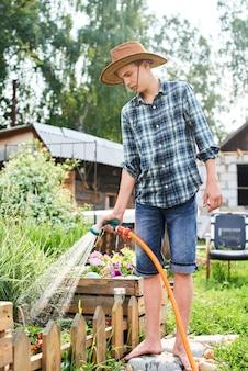 Le gars verse un tuyau de collecte d'eau dans le village