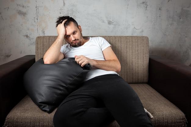 Un gars vêtu d'une chemise blanche est allongé sur le canapé.