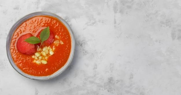 Gaspacho de plat espagnol traditionnel. assiette avec tomate, poivre, purée d'ail avec sauce tabasco sur fond gris béton copie espace