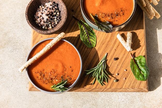 Gaspacho de tomates fraîches avec du poivre moulu, des légumes verts et des grissini ou des bâtonnets de pain