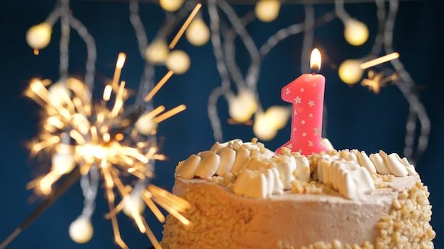 Gâteau d'anniversaire avec 1 bougies roses et cierge magique brûlant sur fond bleu. fermer