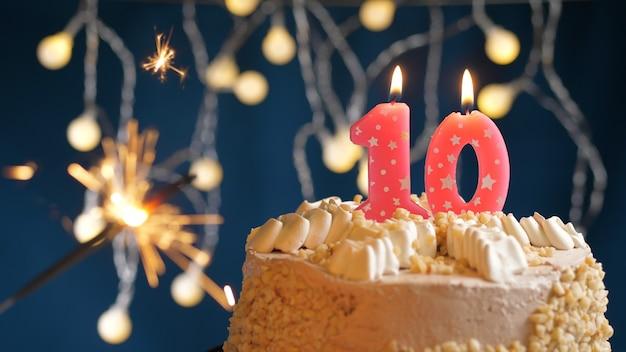 Gâteau d'anniversaire avec 10 bougies roses numérotées et cierge magique brûlant sur fond bleu. fermer