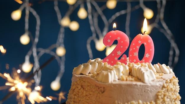 Gâteau d'anniversaire avec 20 bougies roses et cierge magique brûlant sur fond bleu. fermer