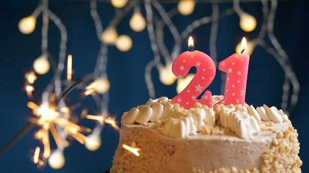Gâteau d'anniversaire avec 21 bougies roses et cierge magique brûlant sur fond bleu. fermer