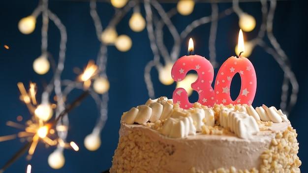 Gâteau d'anniversaire avec 30 bougies roses numérotées et cierge magique brûlant sur fond bleu. fermer