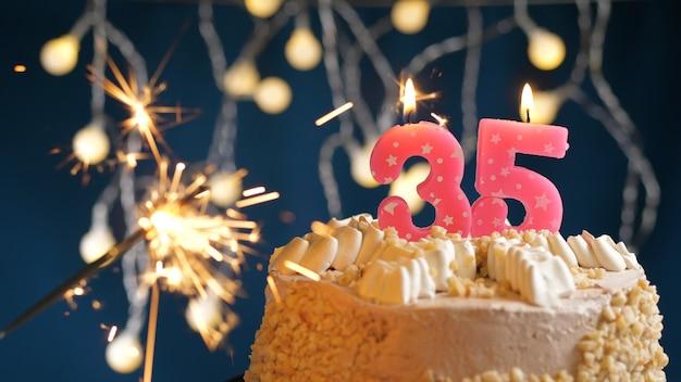 Gâteau d'anniversaire avec 35 bougies roses et cierge magique brûlant sur fond bleu. fermer