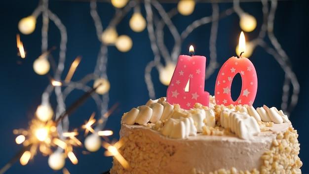 Gâteau d'anniversaire avec 40 bougies roses numérotées et cierge magique brûlant sur fond bleu. fermer
