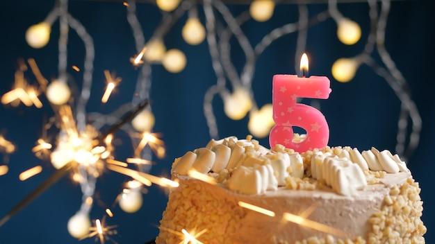 Gâteau d'anniversaire avec 5 bougies roses et cierge magique brûlant sur fond bleu. fermer
